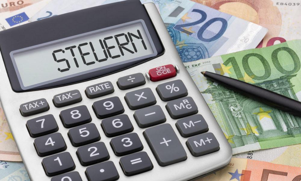 Taschenrechner mit Geldscheinen - Steuern